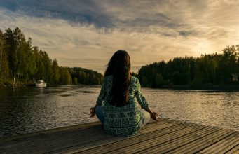 Women doing yoga on lakeside